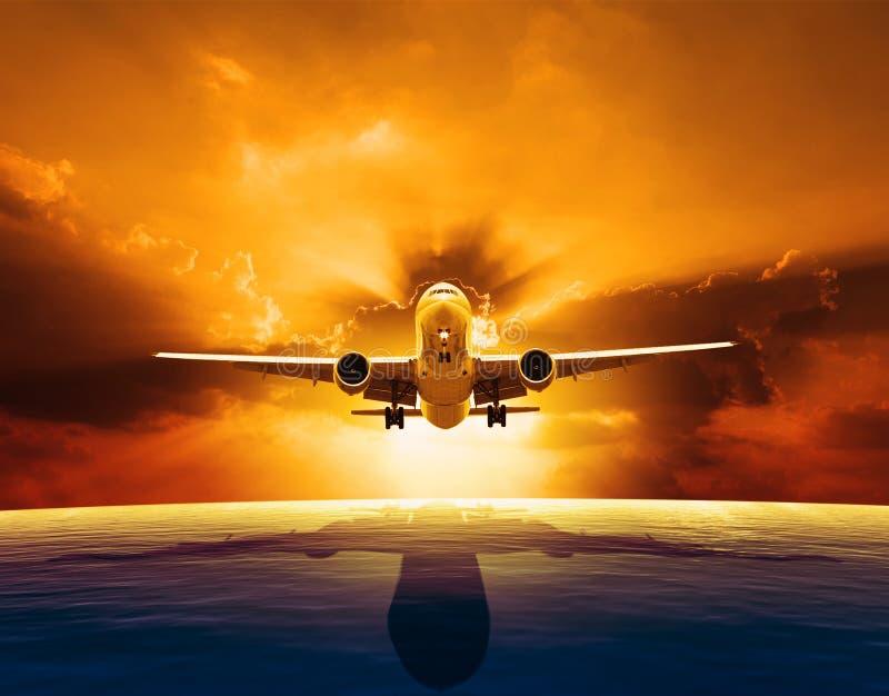 Vol plat d'avion de passagers au-dessus de beau niveau de la mer avec l'ensemble du soleil photo stock