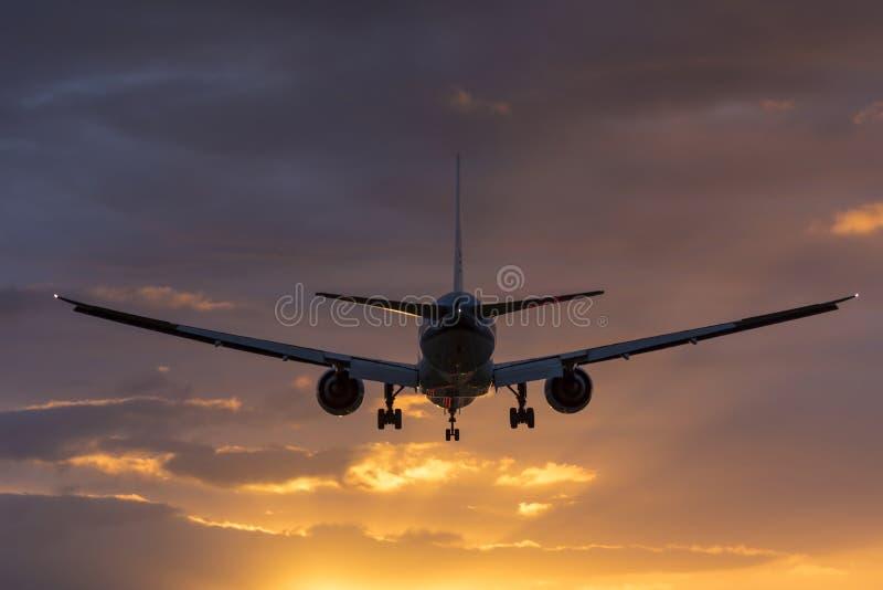 Vol plat vers la piste pendant un lever de soleil nuageux photos stock
