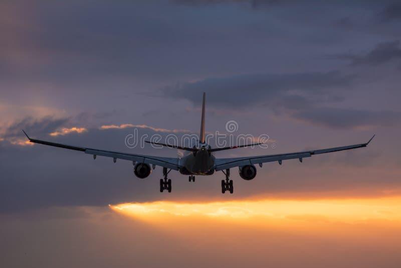 Vol plat vers la piste pendant un lever de soleil nuageux photo stock