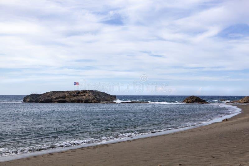 Vol portoricain de drapeau sur une île minuscule outre de la côte image libre de droits