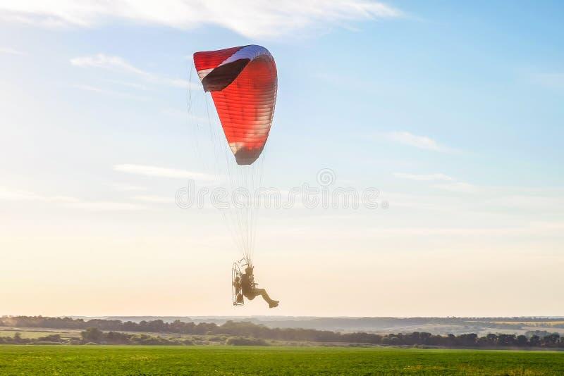 Vol sur un planeur de moteur dans le ciel bleu avec la lumière du soleil lumineuse de contre-jour au-dessus de la plaine de vert photo libre de droits