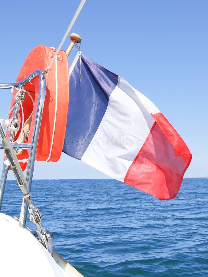 Vol tricolore français de drapeau au dos d'un bateau partant en vent images libres de droits