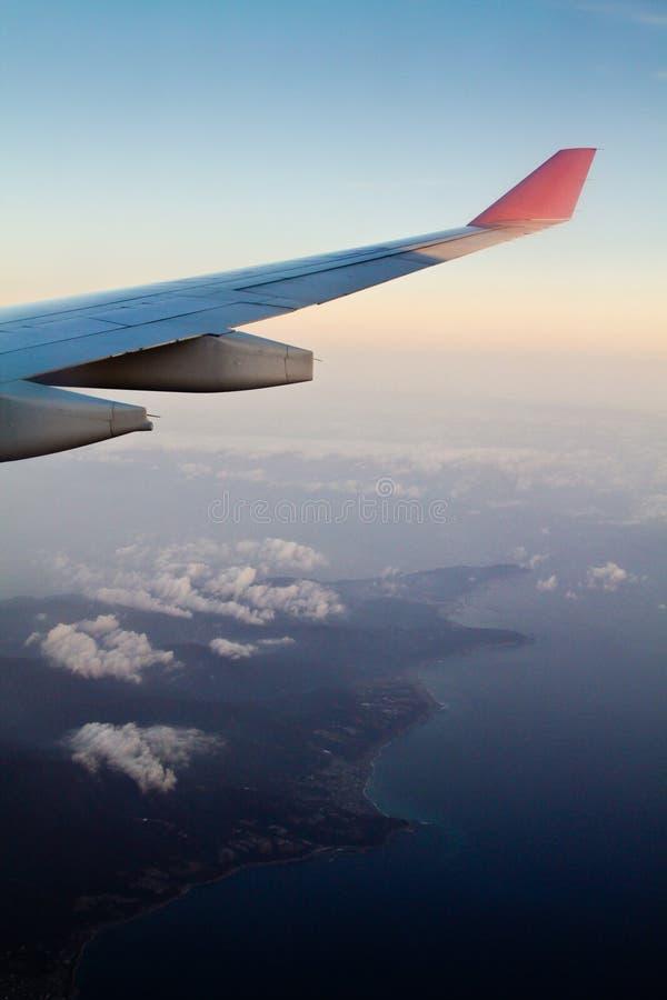 Volando al continente durante il Sun messo fotografia stock