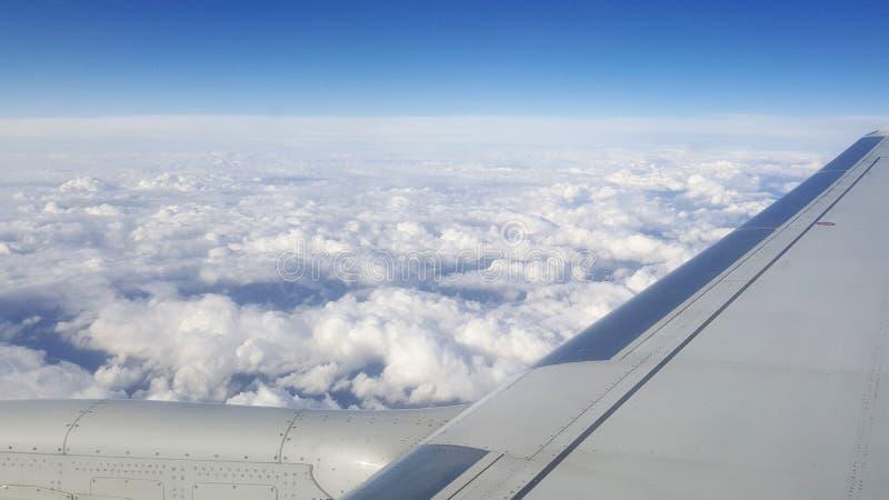 Volando y viajando al extranjero, visión desde la ventana del aeroplano en el ala en el cielo azul nublado a bordo invierno de la fotos de archivo