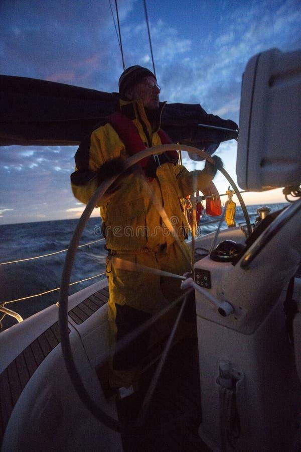 Volant d'homme sur le yacht de navigation pendant le coucher du soleil photographie stock