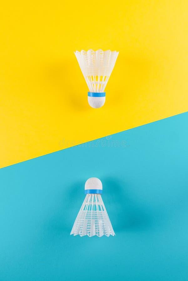 Volant et raquette, badminton sur le fond jaune et bleu Excitation de concept, résistance, concurrence Art de bruit photographie stock libre de droits