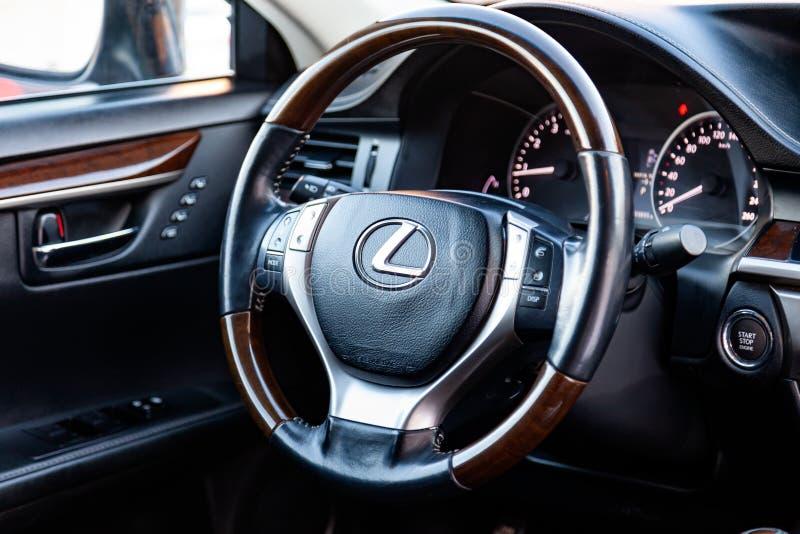 Volante com partes da madeira e para cromar detalhes chapeados no design de interiores de um carro preto luxuoso de Lexus contra fotos de stock