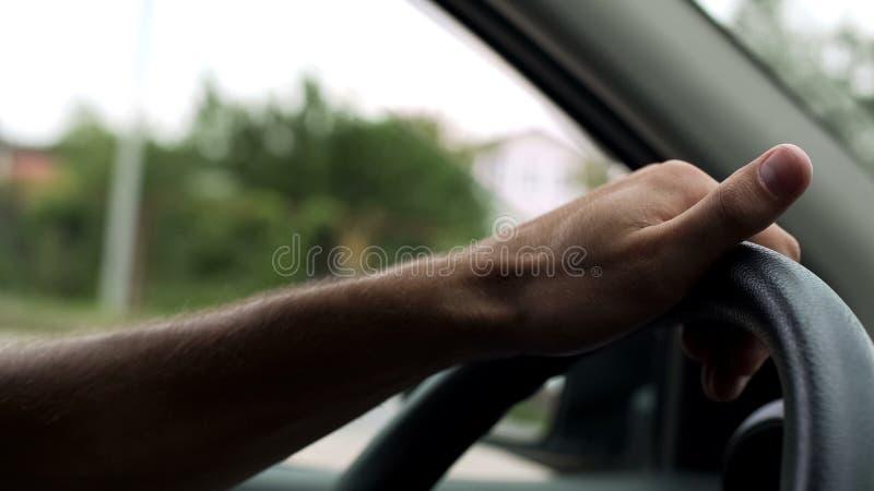 Volante de gerencio do homem com uma mão, lições de condução do carro, instrutor imagens de stock