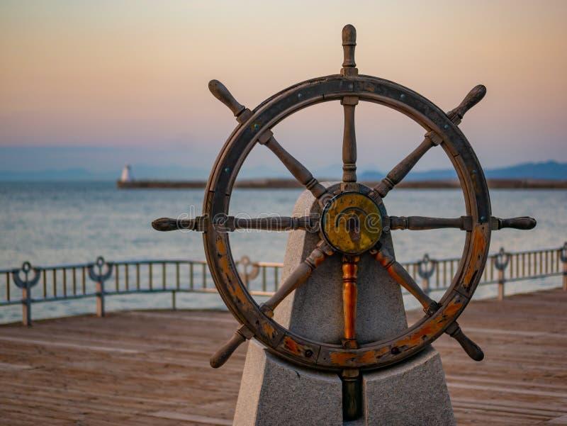 Volante de los capitanes o tim?n de un velero de madera viejo en un puerto en la puesta del sol fotografía de archivo libre de regalías