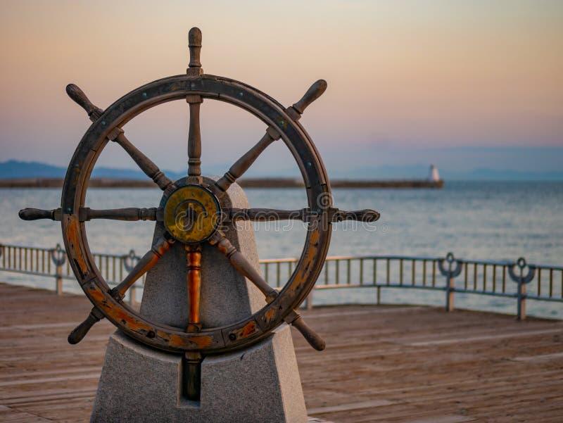 Volante dei capitani o timone di vecchia nave di navigazione di legno in un porto al tramonto fotografia stock libera da diritti