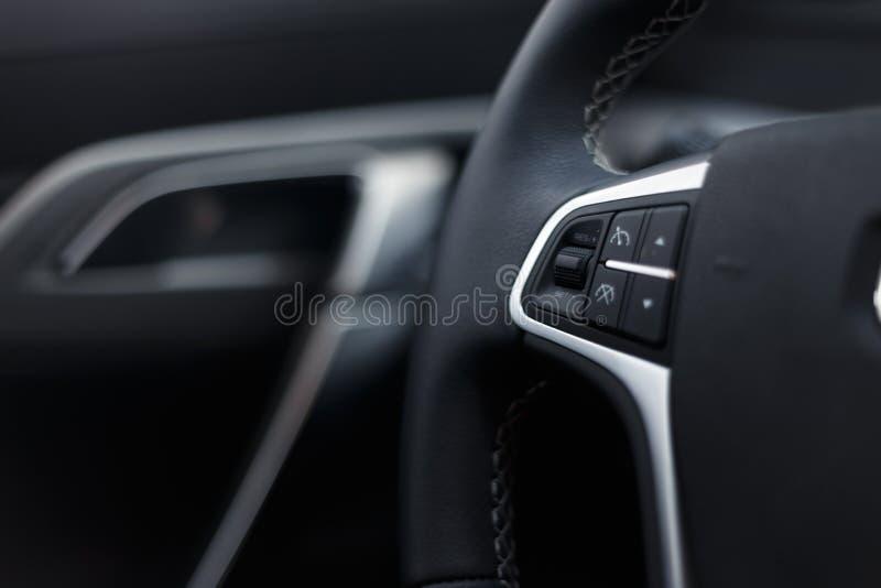 Volante do couro dos multim?dios em um carro caro moderno Volante de couro perfurado imagens de stock