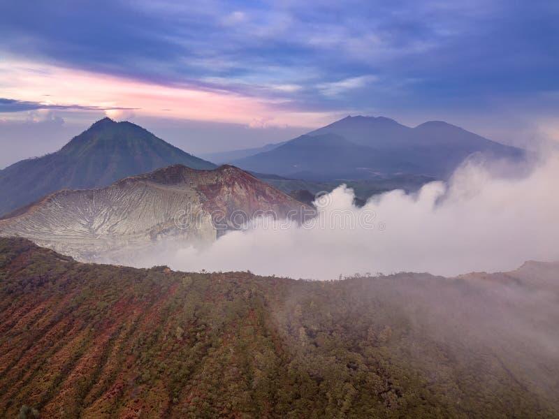 Volcán activo de Ijen en la salida del sol Silueta del hombre de negocios Cowering imagen de archivo libre de regalías