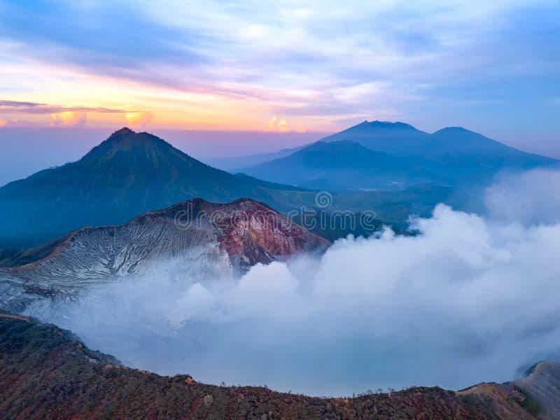 Volcán activo en el amanecer en la isla de Java Silueta del hombre de negocios Cowering fotografía de archivo