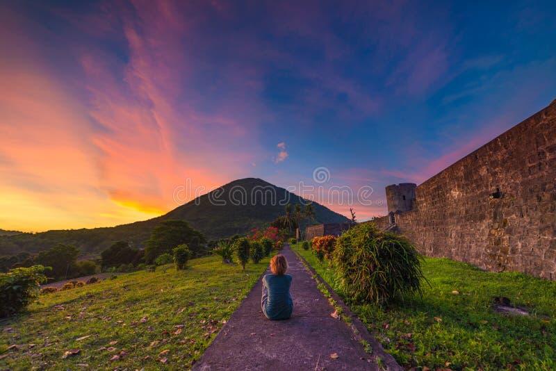 Volcán en la puesta del sol, mujer que se sienta del Api que mira la visión desde el fuerte de Banda Naira, Maluku moluqueños Ind fotografía de archivo libre de regalías