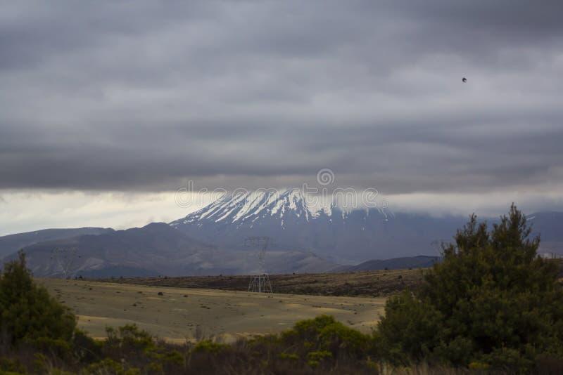 Volcan avec la neige sur le dessus, caché par les nuages orageux images stock