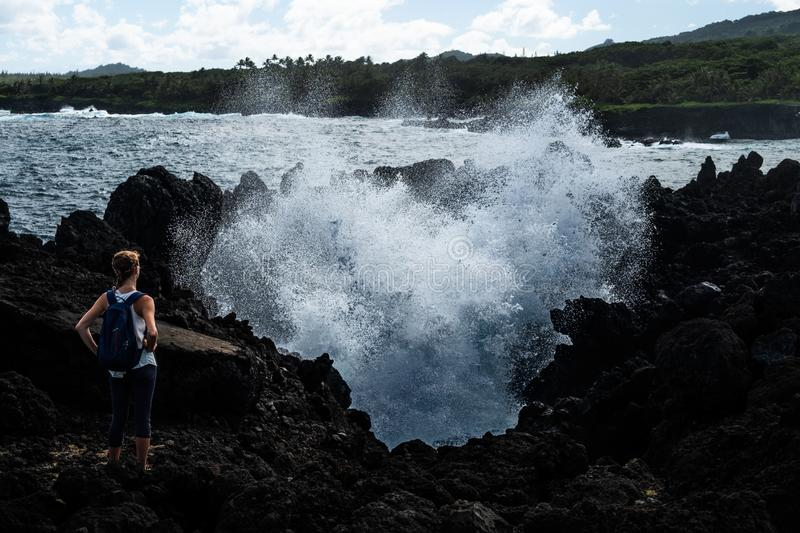 Volcanic coast. Woman hiker stands on the volcanic sharp ground and watches giant splash of the water caused by fierce ocean wave. East coast of Maui, Hawaii stock photography