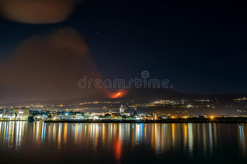 Volcanic eruption and ash plume at nighttime. An impressive volcanic eruption and ash plume generated by volcano Mt. Etna, december 2018, Catania, Sicily, Italy stock image