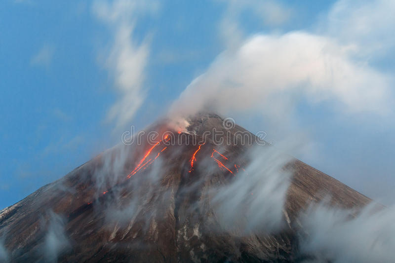 Volcanic eruption - lava flows from crater of volcano. Volcanic landscape: active Klyuchevskoy Volcano, view of top of a volcanic eruption - lava flows on slope royalty free stock photos
