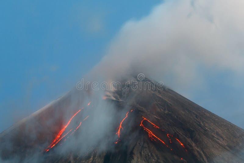 Volcanic eruption - lava flows on slope of volcano. Volcanic landscape of Kamchatka Peninsula: active Klyuchevskaya Sopka, view of top of a volcanic eruption stock photography