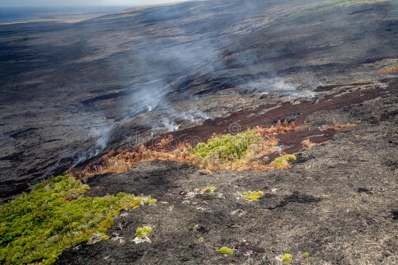 Volcanic landscape. Aerial shot of remaining stands of forest between fresh lava flows and emissions of volcanic fumes on the slopes of the active volcano stock photo