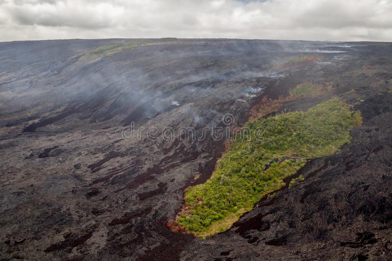 Volcanic landscape. Aerial shot of remaining stands of forest between fresh lava flows and emissions of volcanic fumes on the slopes of the active volcano royalty free stock image