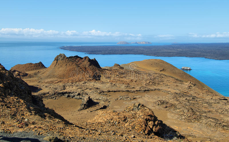 Volcanic lansdscape in Bartolome island. And Santiago island at background, Galapagos, Ecuador stock images