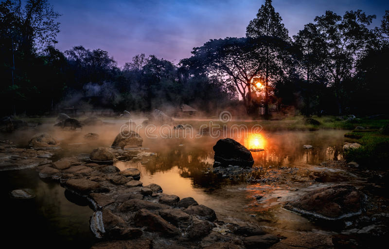 Volcanic natural hot spring mineral water pool with steam spa an. D sun reflect light , travel landmark background ,lampang thailand landscape ,colorful dark royalty free stock photography