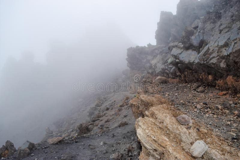 Rock formations against a foggy background at Mount Meru, Tanzania. Volcanic rock formations above the clouds at Mount Meru, Arusha National Park, Tanzania royalty free stock photos