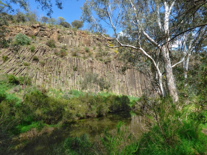 Volcanic rock formations and reflections on the water at the Organ Pipes National Park near Melbourne Australia royalty free stock images