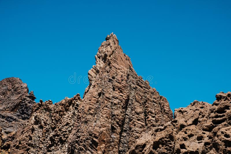 Volcanic rock , layered volcanic rock in desert with mountain landscape and blue sky royalty free stock image