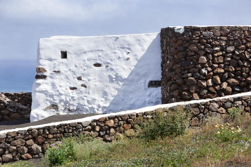 Volcanic stones and white concrete building walls. On Lanzarote in Spain royalty free stock photos