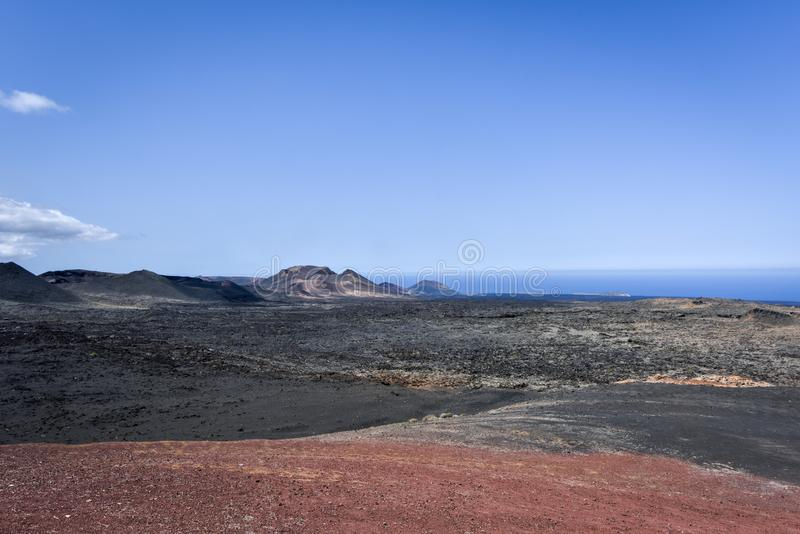 Volcanic Timanfaya National Park with volcano and the sea in the background, Lanzarote royalty free stock images