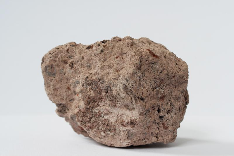 Volcanic tuff mineral on white background. Volcanic tuff from Kamchatka region of Russian Federation on white background potentially for economic news on stock photo