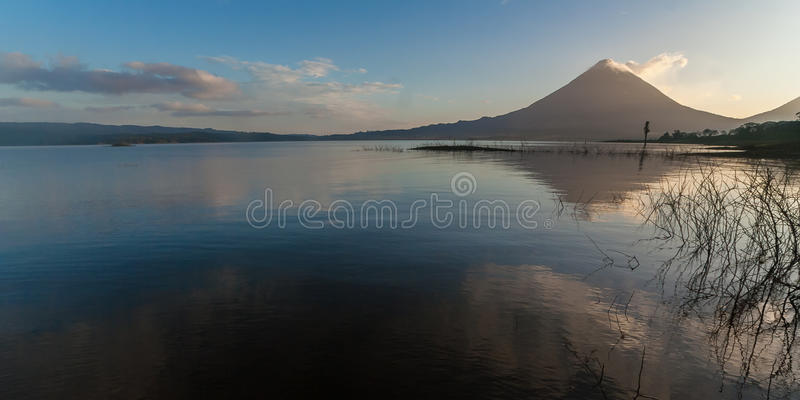 Volcano Arenal in the early morning with reflection in the water. Volcano Arenal in Costa Rica at dawn with reflection in the water stock photography