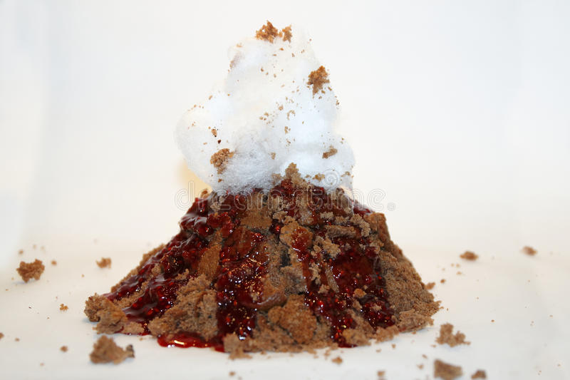 Volcano cake with red berry sauce lava and candy floss royalty free stock images