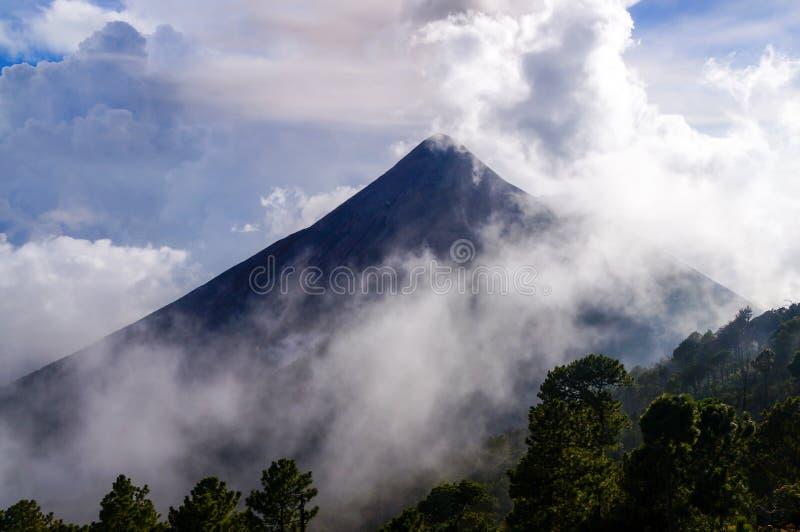 Volcano Fuego täckte vid moln och mist arkivfoto
