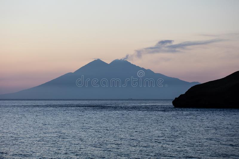 Volcano Silhouette in Indonesia`s Ring of Fire. Smoke billows from the top of Sangeang Api, an active volcano just outside of Komodo National Park, Indonesia stock image