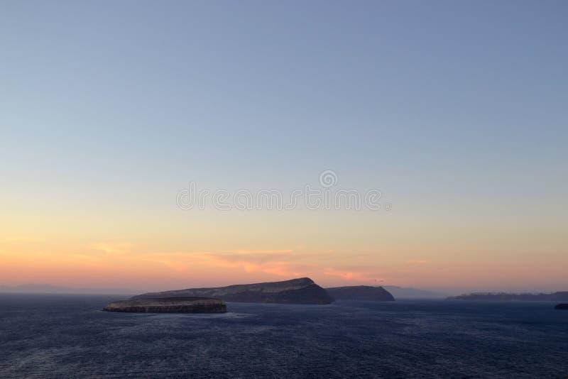 Volcano at sunset in Santorini. Volcano end sea at sunset in Santorini stock image