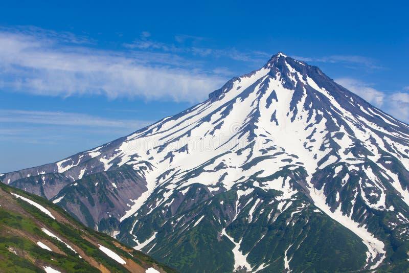 Volcano Viluchinsky omvat met sneeuw bij zonnige de zomerdag, het Schiereiland van Kamchatka stock fotografie