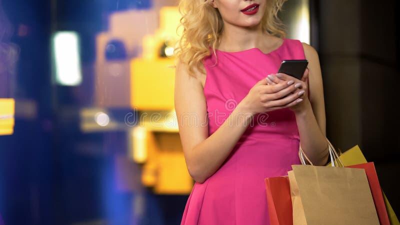 Voldaan aan dame het typen bericht op smartphone, het succesvolle winkelen, kortingen stock afbeeldingen