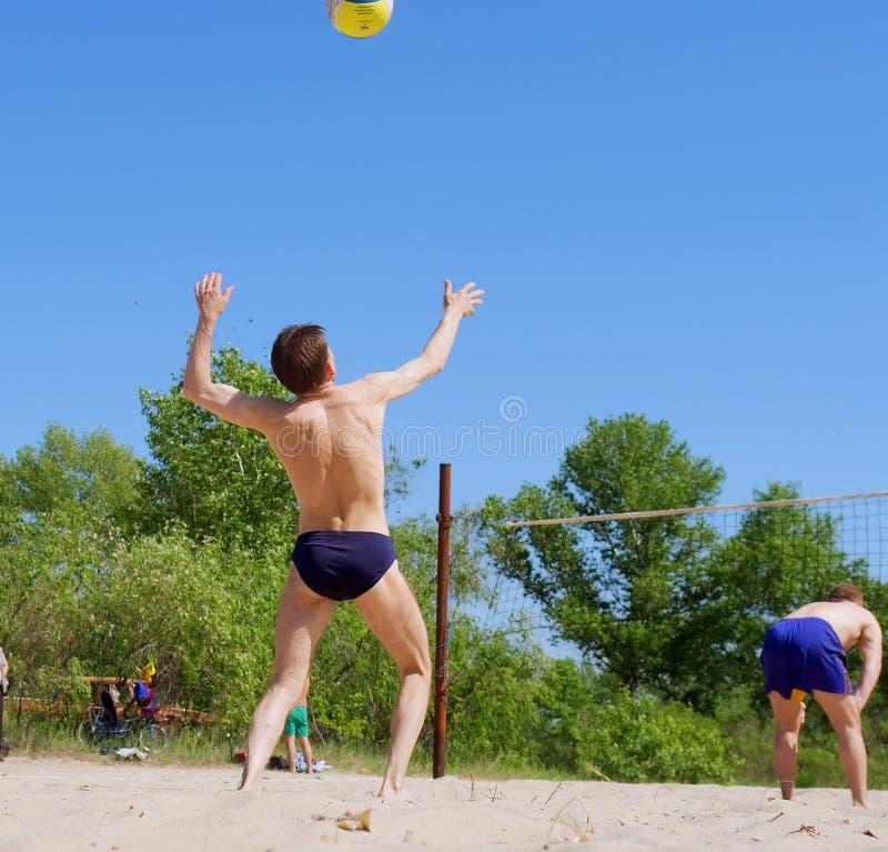 Voleibol da praia do jogo de dois homens imagens de stock