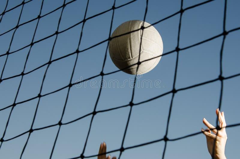 Voleibol detrás de la red con las manos fotografía de archivo