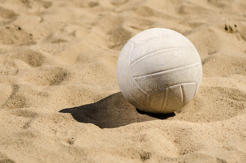 Voleibol que se sienta en arena imagen de archivo