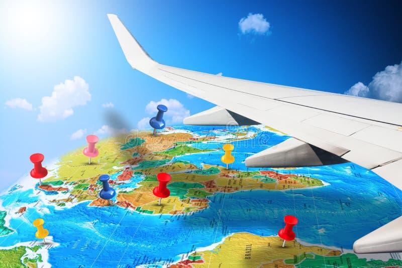 Voler autour du monde avec l'aile d'avions éclipsant la carte de la terre avec des goupilles marquant de futures destinations images libres de droits