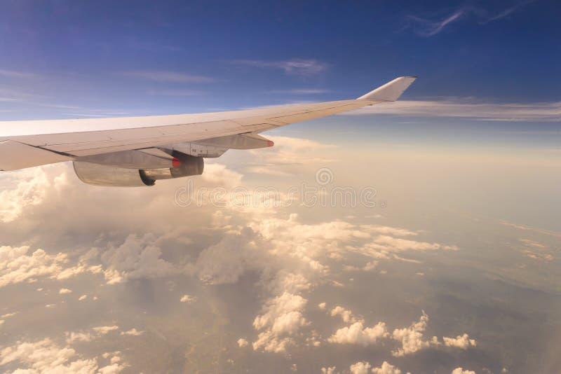 Voler dans le ciel de coucher du soleil et la mer des nuages et de l'aile des WI d'avion image stock