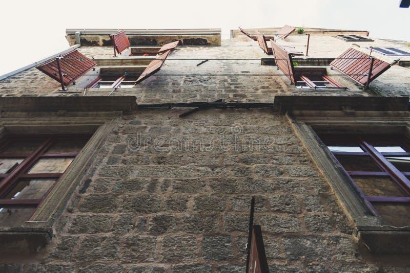 Volets ouverts des fenêtres sur un vieux mur en pierre Vue inf?rieure Construction avec de la corde à linge en dehors de la fenêt photographie stock