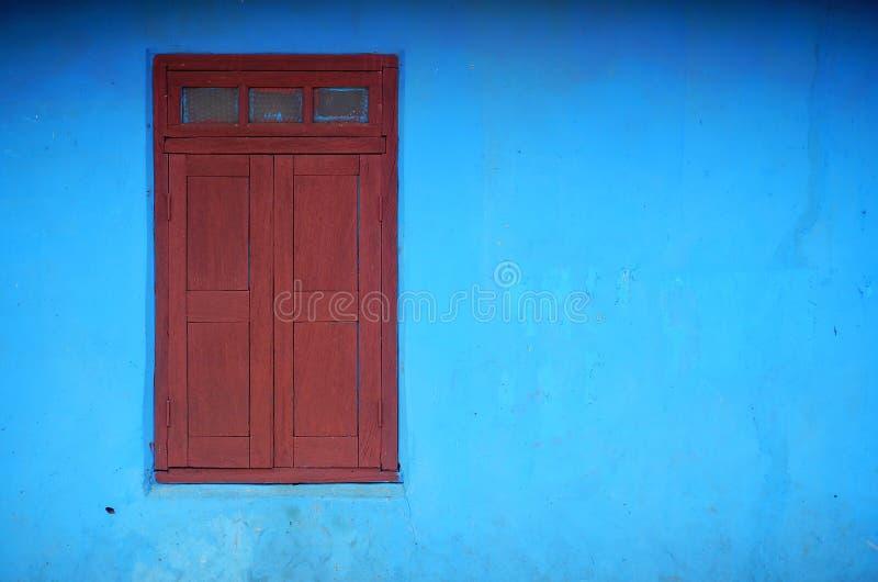Volets rouges dans le mur bleu image libre de droits