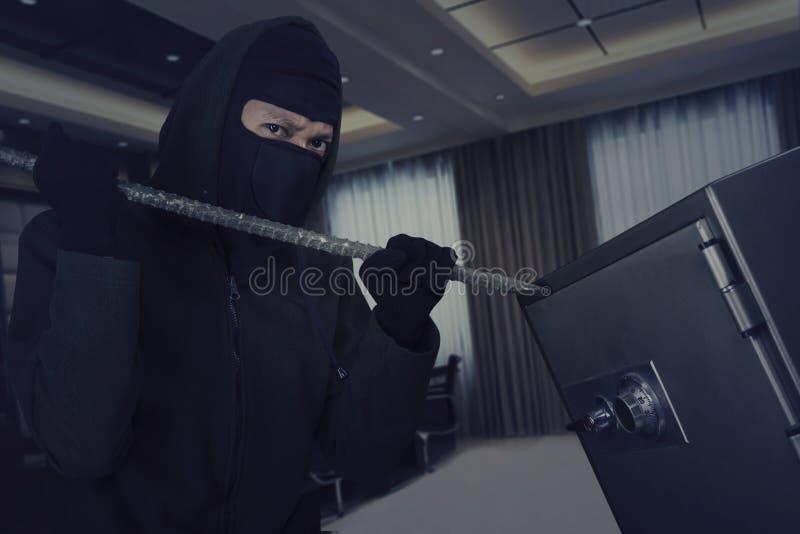 Voleur à l'aide du pied-de-biche pour ouvrir la chambre forte de banque photo stock