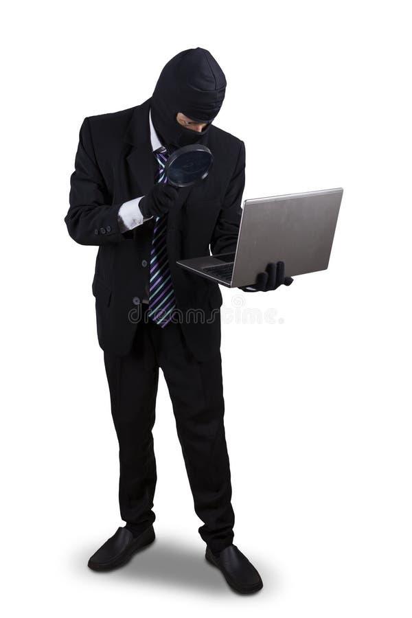 Voleur avec la loupe et l'ordinateur portable image libre de droits