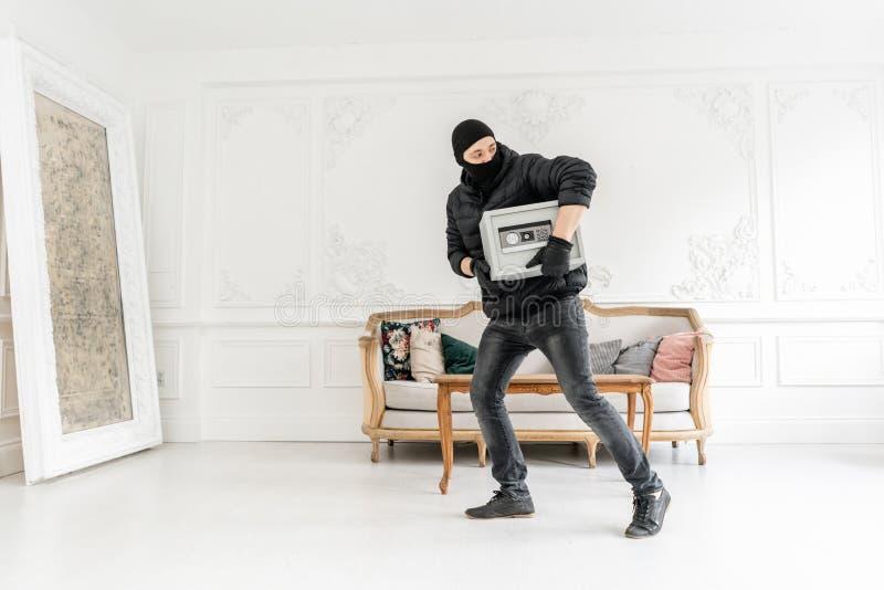 Voleur avec le passe-montagne noir volant la boîte sûre électronique moderne Le cambrioleur commet un crime en appartement de lux photos stock